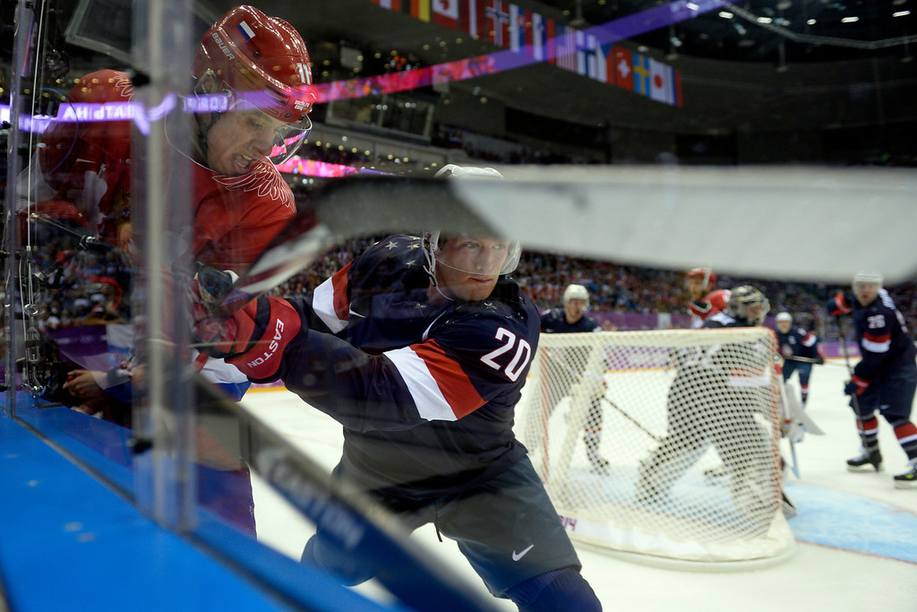 . SOCHI, RUSSIA - FEBRUARY 15: Ryan Suter (20) of the U.S.A. checks Yevgeni Malkin (11) of the Russia into the boards during the second period of men\'s hockey action at Bolshoy arena. Sochi 2014 Winter Olympics on Saturday, February 15, 2014. (Photo by AAron Ontiveroz/The Denver Post)