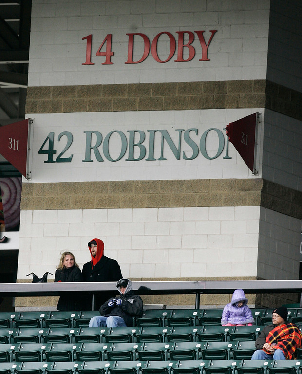 . Fans watch the game between the Cleveland Indians and the Chicago White Sox during the second inning of a baseball game, Sunday, April 15, 2007, in Cleveland.  The Indians won 2-1. Jackie Robinson\'s No. 42 isn\'t the only number with special meaning to the Cleveland Indians. Less than three months after Robinson shattered baseball\'s racial barrier in 1947 with the Brooklyn Dodgers, Larry Doby made his debut for the Indians, becoming the AL\'s first black player. (AP Photo/Tony Dejak)