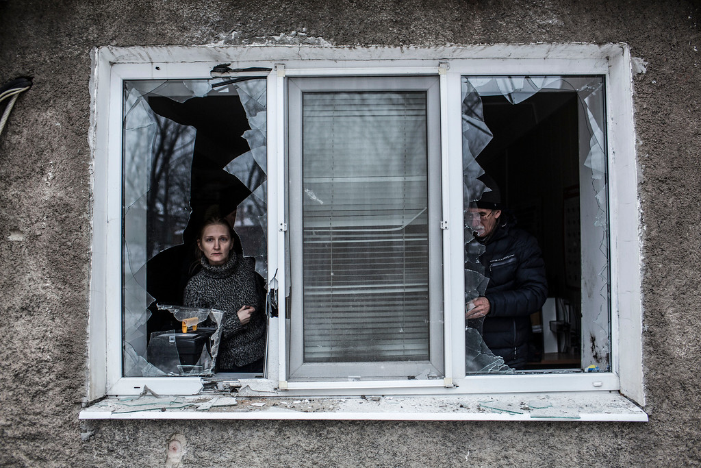 . A Ukrainian woman looks through a broken window at their flat after it was hit by Ukrainian Artillery in the Voroshilovsky area, center of Donetsk, Ukraine. Sunday, Jan. 18, 2015. The separatist stronghold, Donetsk, was shaken by intense outgoing and incoming artillery fire as a bitter battle raged for control over the city\'s airport. Streets in the city, which was home to 1 million people before unrest erupted in spring, were completely deserted and the windows of apartments in the center rattled from incessant rocket and mortar fire. (AP Photo/Manu Brabo)