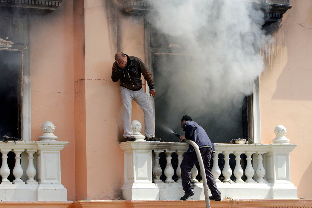 . Policemen try to extinguish fire at a police club set by protesters following a court verdict in Cairo, Egypt, Saturday, March 9, 2013. Fans of Cairo\'s Al-Ahly club have stormed Egypt\'s soccer federation headquarters, set it ablaze after a court acquitted seven of nine police officials on trial for their alleged part in deadly stadium melee. A fire also broke out Saturday in a nearby police club, but it was not immediately known whether Al-Ahly fans started the blaze there too. (AP Photo/Amr Nabil)