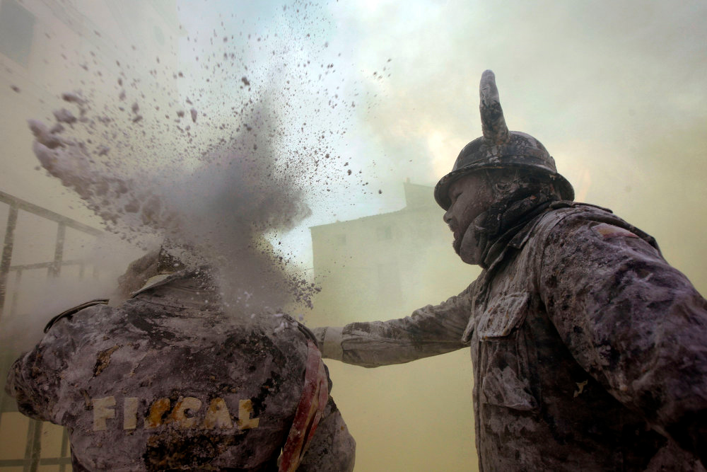 Description of . Revelers take part in festival of Els Enfarinats, in the town of Ibi near Alicante, Spain, Friday, Dec. 28, 2012. For 200 years the inhabitants of Ibi annually celebrate with a battle using flour, eggs and firecrackers, outside the city town hall. (AP Photo/Alberto Saiz)