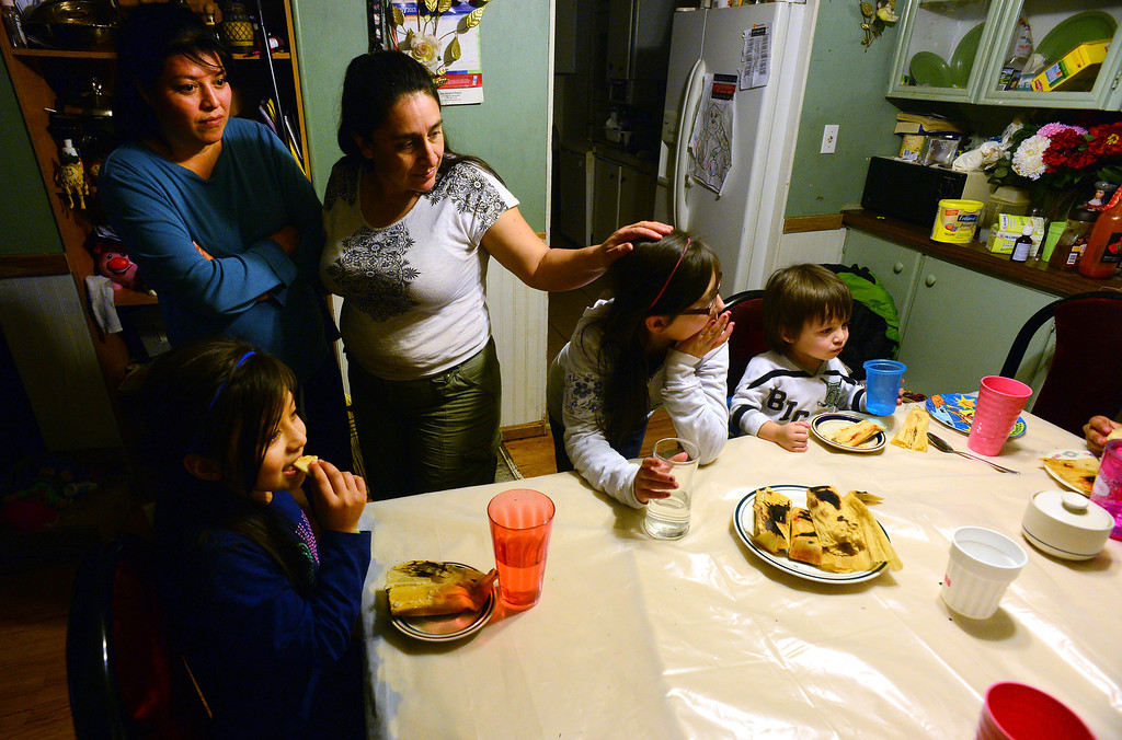 . GREELEY, CO - DECEMBER 16, 2013: Norma Meza strokes the hair of Janeth Moreno, 10 during dinner as Janeth\'s mother Rosario watches the crew as they eat at Meza\'s tiny house  in Greeley, CO on December 16, 2013. The Meza family, which consists of four children, Norma and her husband Martin have taken in the Moreno family after they lost everything in the September floods.  Rosario and her husband Jose have 5 children and are without a home at the moment.  Norma says she will help out her best friend for as long as she needs to.  The tiny house has 3 bedrooms and 2 small bathrooms and is home now to 14 people, 2 cats and 3 dogs.  Also in the photo are from left to right  Yanna Moreno, 8, and Edwin Moreno, 2. (Photo By Helen H. Richardson/ The Denver Post)