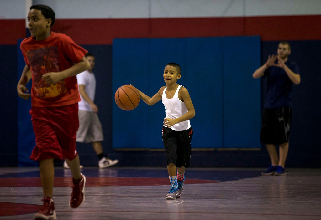 . Downey Christian high school varsity basketball player 11-year-old Julian Newman (C) dribbles the ball up court during Friday evening pickup basketball games at Downey Christian School in Orlando, Florida February 22, 2013. At 4 feet 5 inches tall, starting point guard Julian Newman stands waist high next to other players on his Florida high school basketball team. But his talent towers over the competition. At only 11, Newman leads the state of Florida in assists per game this season and ranks fifth nationally, according to Maxpreps.com, which maintains statistics on high school sports.  REUTERS/Scott Audette