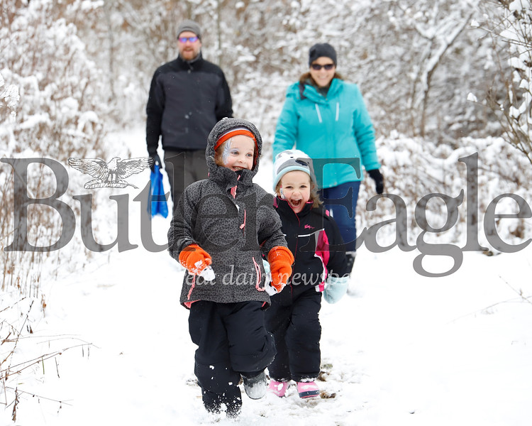 Genevieve, 5,(left) and Abigail Little, 4, race ahead of their parents KC and Kevin Little of Zelienople on a walk near the Butterfly gardens on Moraine State Park's North Shore Saturday, during Winterfest. Seb Foltz/Butler Eagle 02/08/20