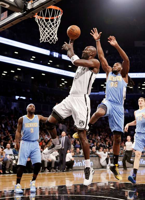 . Denver Nuggets forward Kenneth Faried (35) defends as Brooklyn Nets forward Kevin Garnett (2) goes up for a layup in the first half of an NBA basketball game Tuesday, Dec. 3, 2013, in New York. (AP Photo/Kathy Willens)