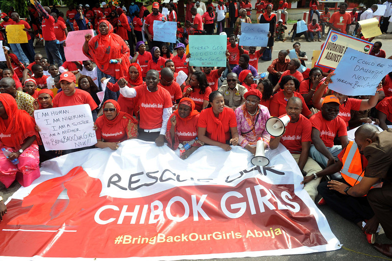 ". Members of civil society groups sit to protest the abduction of Chibok school girls during a rally pressing for the girls\' release in Abuja on May 6, 2014, ahead of World Economic Forum. Members of civil society groups marched through the streets of Abuja and to the Nigerian defence headquarters to meet with military chiefs, to press for the release of more than 200 Chibok school girls abducted three weeks ago. Suspected Boko Haram Islamists have kidnapped eight more girls from Nigeria\'s embattled northeast, residents said on May 6, after the extremist group\'s leader claimed responsibility for abducting more than 200 schoolgirls last month and said in a video he was holding them as ""slaves\"" and threatened to \""sell them in the market\"".  (PIUS UTOMI EKPEI/AFP/Getty Images)"