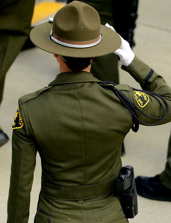 . A San Diego County Sheriff Deputy salutes the casket of San Bernardino County Sheriff Deputy Jeremiah MacKay during memorial services held at the San Manuel Amphitheater in Devore February 21, 2013.  GABRIEL LUIS ACOSTA/STAFF PHOTOGRAPHER.