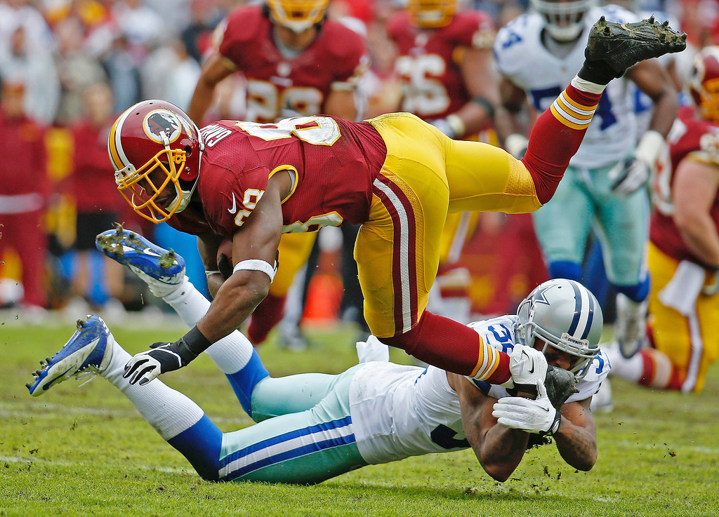 . Washington Redskins wide receiver Pierre Garcon is upended by Dallas Cowboys cornerback Orlando Scandrick during the first half of an NFL football game in Landover, Md., Sunday, Dec. 22, 2013. (AP Photo/Alex Brandon)
