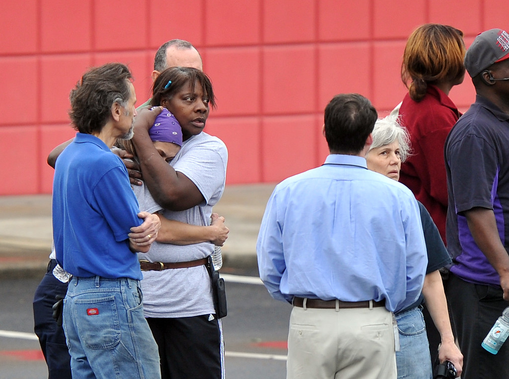 . FedEx Employee Lisa Aiken, is embraced by a co-worker as other FedEx employees gather a skating rink following a shooting at the FedEx facility in Kennesaw, Ga., on Tuesday, April 29, 2014.   (AP Photo/Atlanta Journal-Constitution, Brant Sanderlin)