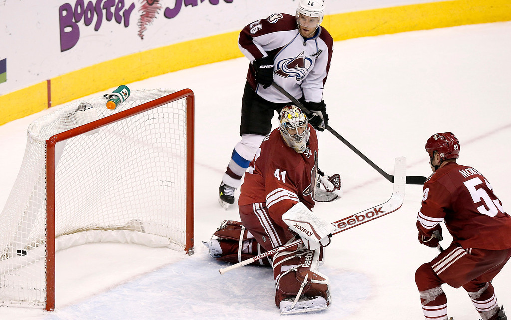 . Phoenix Coyotes\' Mike Smith (41) gives up the game-winning goal to Colorado Avalanche\'s Ryan O\'Reilly as the Avalanche\'s Paul Stastny (26) and the Coyotes\' Derek Morris (53) look on during overtime of an NHL hockey game Thursday, Nov. 21, 2013, in Glendale, Ariz.  The Avalanche defeated the Coyotes 4-3. (AP Photo/Ross D. Franklin)