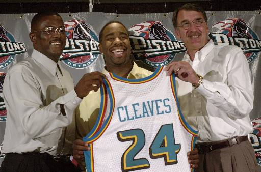 Description of . Mateen Cleaves, center, holds a Detroit Pistons jersey with his high school number with President of Basketball Operations Joe Dumars, left, and head coach George Irvine at The Palace in Auburn Hills, Mich., during a news conference with the Pistons first round draft choice. (AP Photo/Paul Sancya)