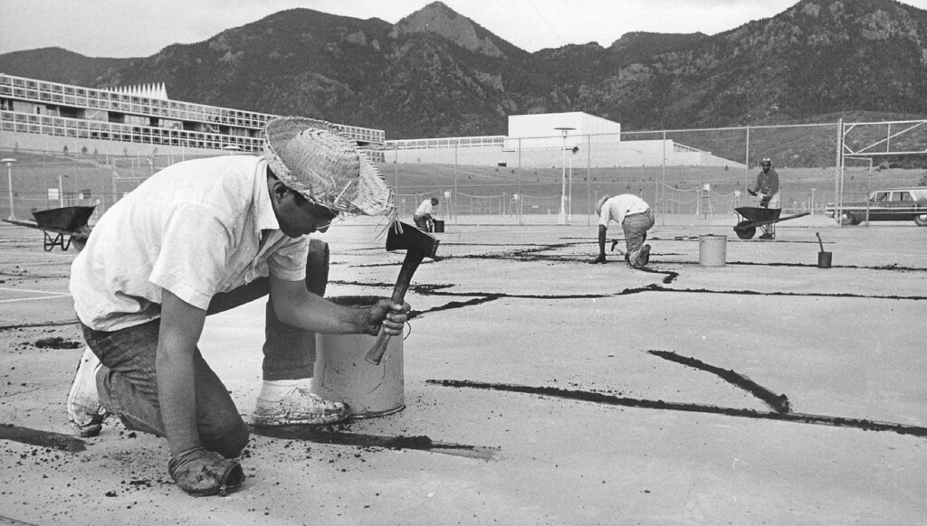 """. Construction worker Frank Macias of Denver repairs the cracks in a tennis court with bitumen cement. Like any \""""city,\"""" the Air Force Academy has recreation facilities and park areas for the enjoyment of its 10,522 residents.  1965. The Denver Post Library Archive"""