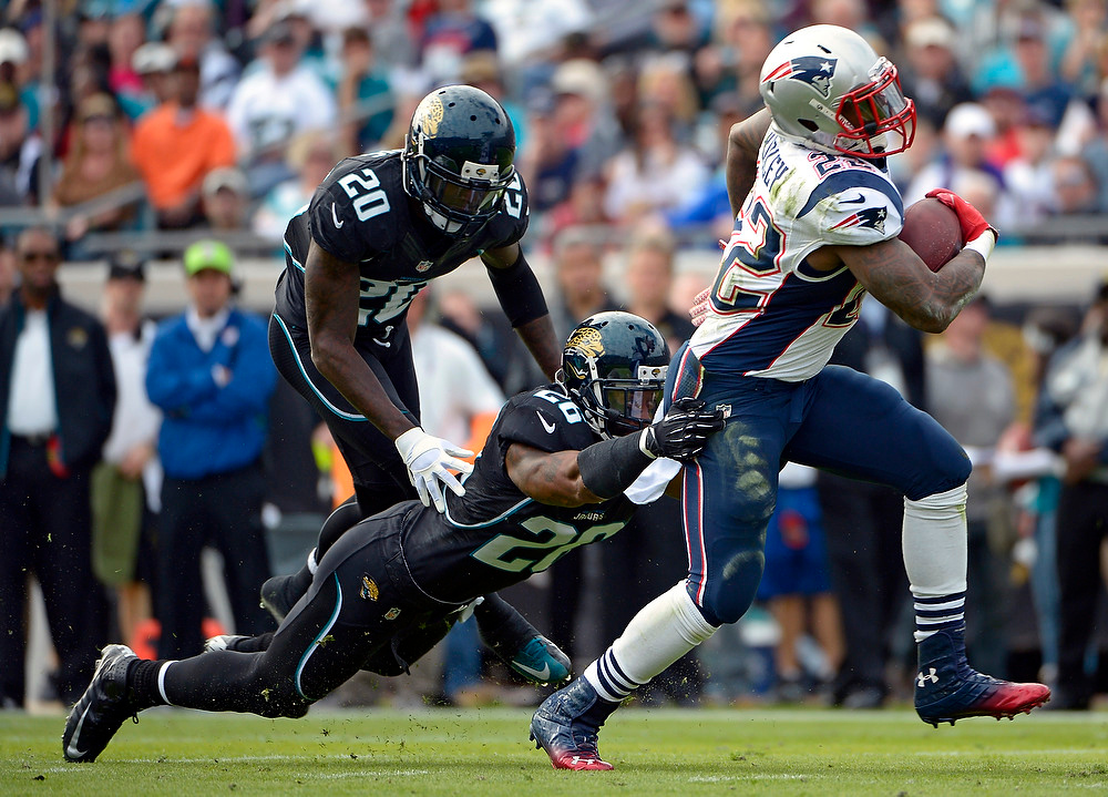 . New England Patriots running back Stevan Ridley (22) runs for yardage past Jacksonville Jaguars strong safety Dawan Landry (26) and cornerback Mike Harris (20) during the first half of an NFL football game on Sunday, Dec.  23, 2012, in Jacksonville, Fla. (AP Photo/Phelan M. Ebenhack)
