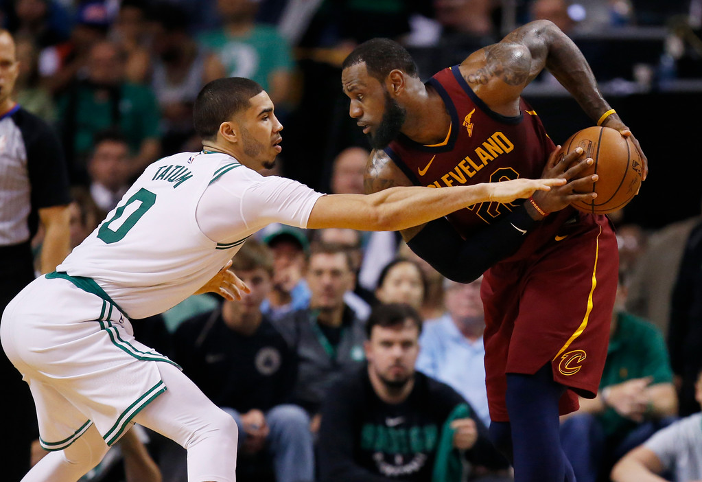 . Cleveland Cavaliers forward LeBron James, right, looks to make a move against Boston Celtics forward Jayson Tatum (0) during the second half of Game 1 of the NBA basketball Eastern Conference Finals, Sunday, May 13, 2018, in Boston. (AP Photo/Michael Dwyer)