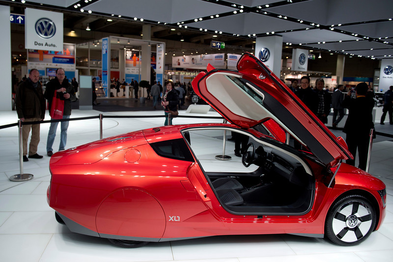 . Visitors look at the Volkswagen XL1 concept car at VW\'s booth at the industrial trade fair in Hanover, central Germany on April 8, 2013. The fair running from April 8 to 12, 2013 presents a cross section of key industrial technologies.  ODD ANDERSEN/AFP/Getty Images