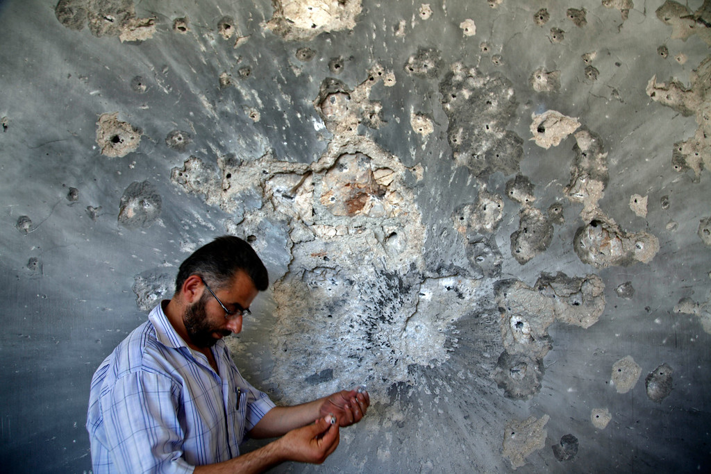 . FILE - A Syrian man holds bullets he picked from the wall of a damaged house in the town of Atareb, on the outskirts of Aleppo, Syria, Sunday, Aug. 5, 2012. (AP Photo/Khalil Hamra, File)