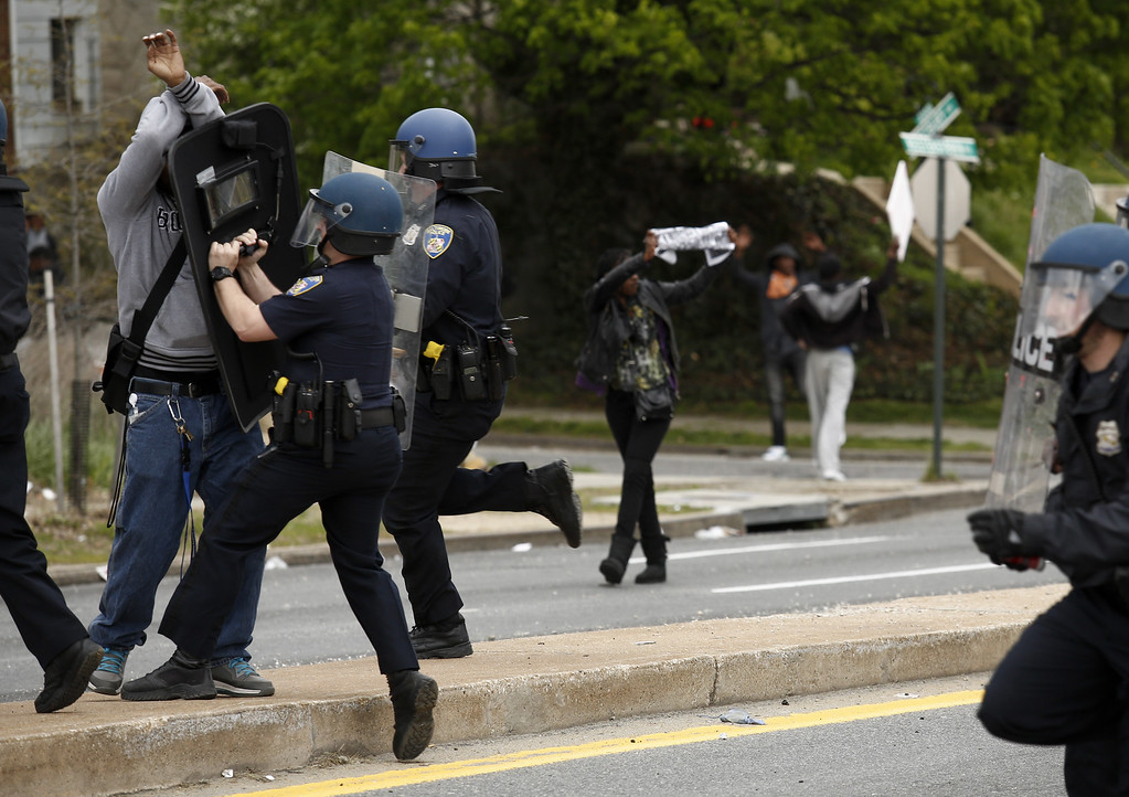 . BALTIMORE, MD - APRIL 27:  Baltimore Police officers  push back a protestor on Reisterstown Road near Mowdamin Mall, April 27, 2015 in Baltimore, Maryland. The funeral service for Freddie Gray, who died last week while in Baltimore Police custody, was held on Monday morning. (Drew Angerer/Getty Images)