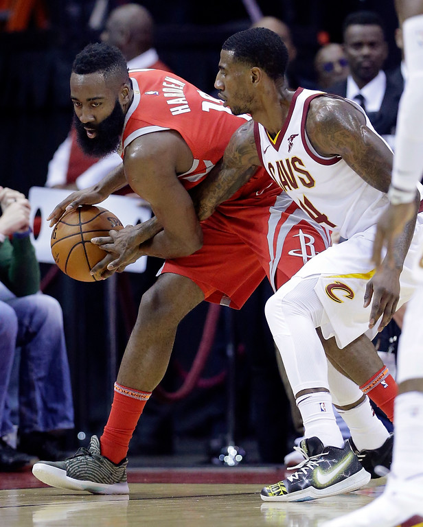 . Houston Rockets guard James Harden (13) keeps the ball from the reach of Cleveland Cavaliers guard Iman Shumpert (4) during the first half of an NBA basketball game Thursday, Nov. 9, 2017, in Houston. (AP Photo/Michael Wyke)
