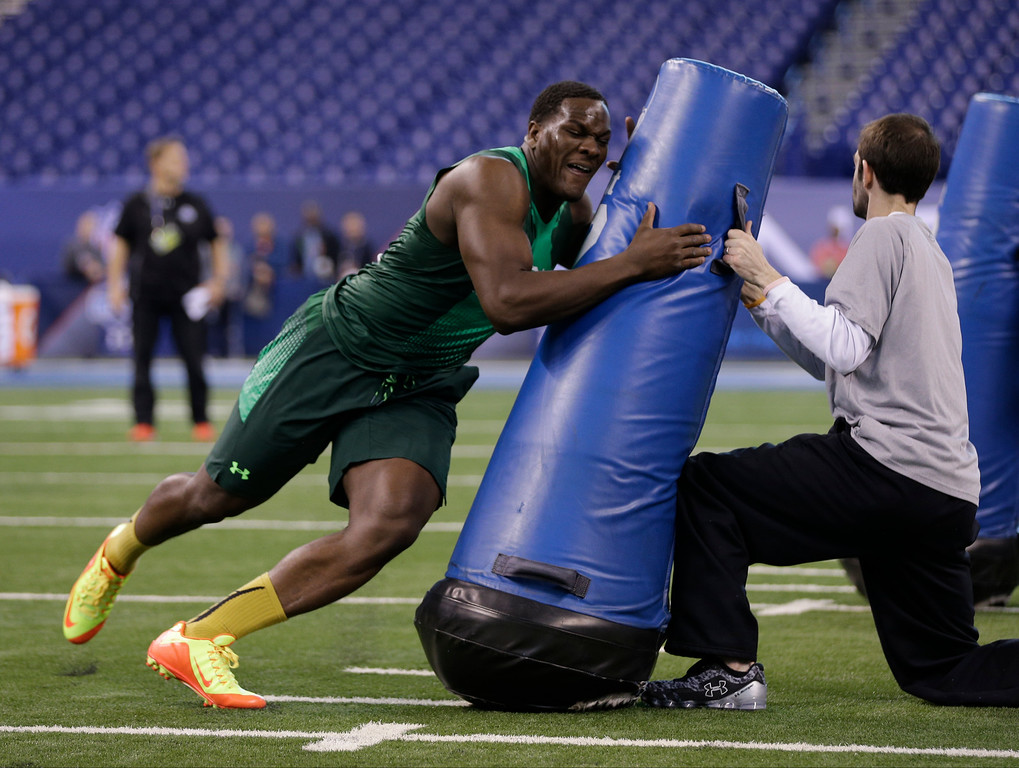 . Michigan defensive lineman Frank Clark runs a drill at the NFL football scouting combine in Indianapolis, Sunday, Feb. 22, 2015. (AP Photo/David J. Phillip)