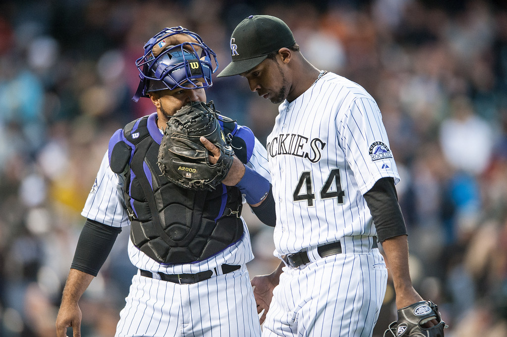 . Juan Nicasio #44 and Wilin Rosario #20 of the Colorado Rockies walk off the field after a scoreless frame during a game against the New York Yankees during a game at Coors Field on May 8, 2013 in Denver, Colorado.  (Photo by Dustin Bradford/Getty Images)
