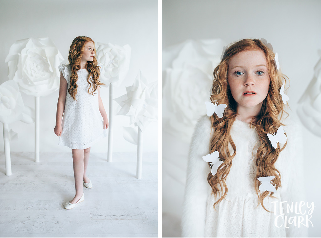 Girl with giant paper flowers and butterflies.Whimsical kid's fashion editorial with giant white paper origami props. Photography by Tenley Clark.