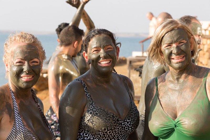 Women smeared with mud from the Dead Sea