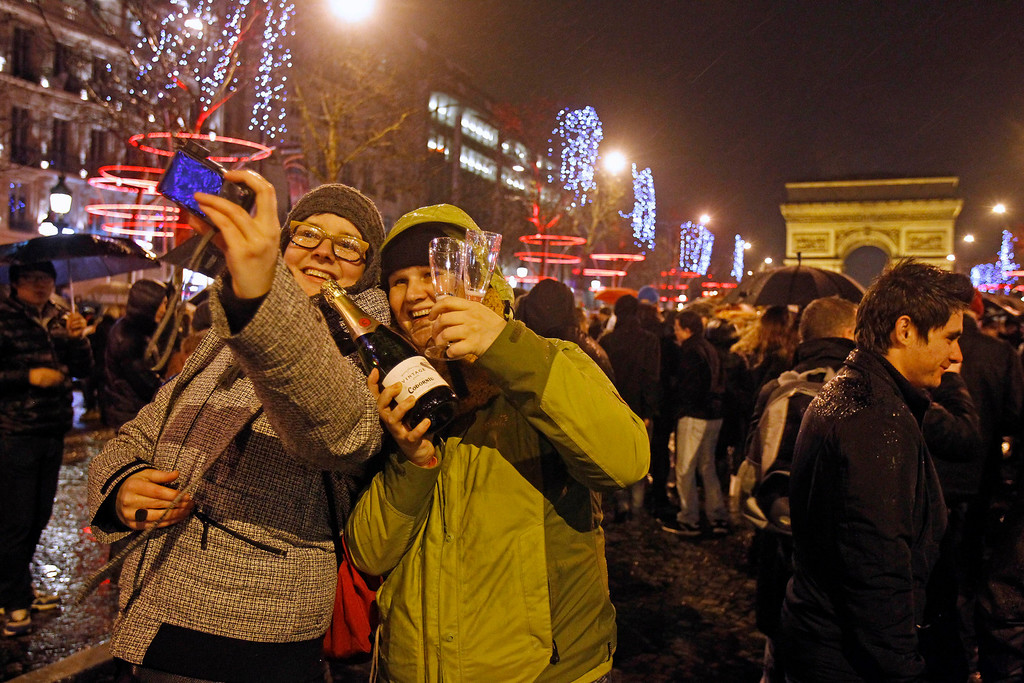 . Revelers celebrate the New Year on the Champs Elysee in Paris, Tuesday Jan. 1, 2013.(AP Photo/Remy de la Mauviniere)