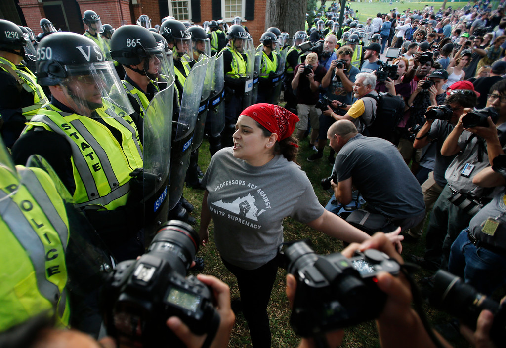 . A protester confronts riot gear-clad police on the campus of the University of Virginia during a rally to mark the anniversary of last year\'s Unite the Right rally in Charlottesville, Va., Saturday, Aug. 11, 2018. (AP Photo/Steve Helber)