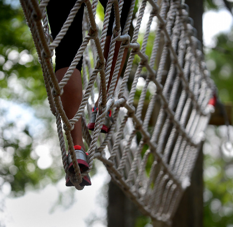 . A woman crosses a rope bridge on the challenge course at the Aerial Adventure Park at Trollhaugen. (Pioneer Press: Chris Polydoroff)