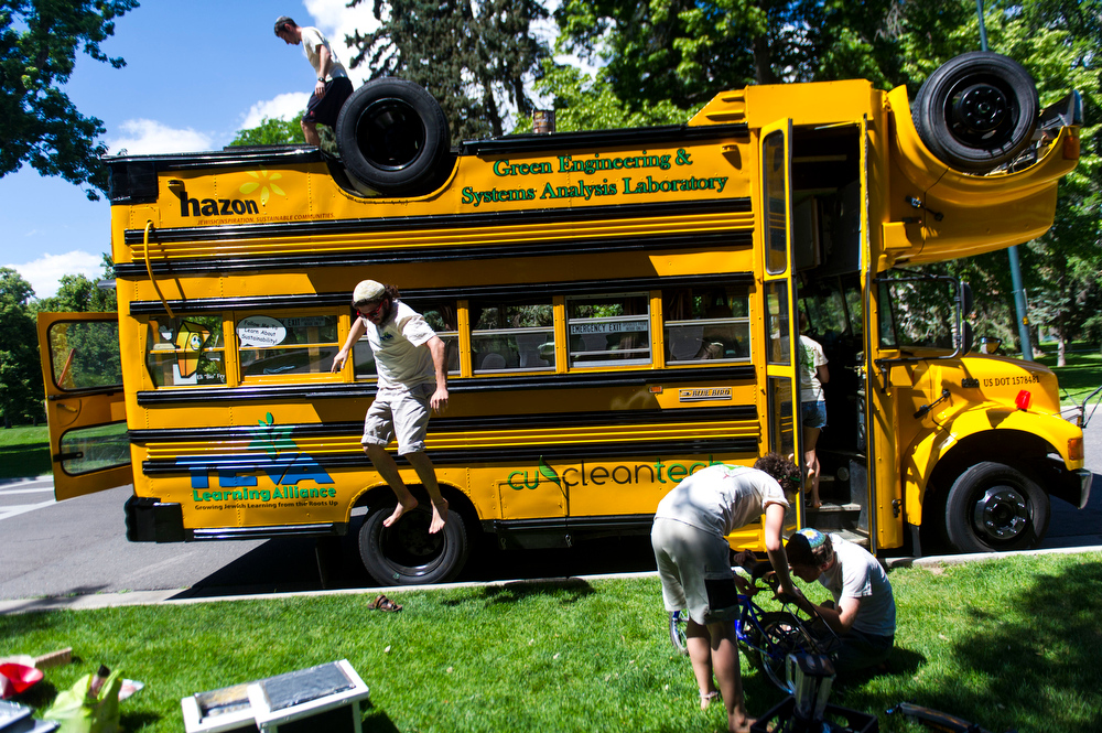 . Benji Elson of New Jersey, jumps down from the roof of the Topsy Turvy Bus while Sonia Wilk, and Jacob Chatinover work on setting up the bicycle powered smoothie blender at Cheeseman Park on Friday, June 27, 2014 in Denver, CO.  The bus was originally made for Ben and Jerry\'s to promo a new flavor; it was later donated to Hazon.  This summer, the bus will travel from Colorado to Connecticut.  (Photo by Kent Nishimura/The Denver Post)