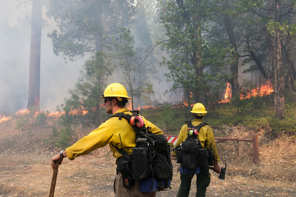 . Two firefighters watch trees burn while battling the Rim Fire near Yosemite National Park, Calif., on Monday, Aug. 26, 2013. Crews working to contain one of California\'s largest-ever wildfires gained some ground Monday against the flames threatening San Francisco\'s water supply, several towns near Yosemite National Park and historic giant sequoias. (AP Photo/Jae C. Hong)