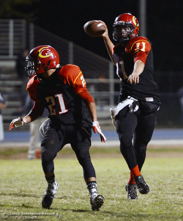 . Chico High\'s #21 Cameron Alfaro (left) runs ahead as #11 Clayton Welch (right) throws a pass against Central Valley High in the first quarter of their football game at Asgard Yard Friday, September 27, 2013, in Chico, Calif.  (Jason Halley/Chico Enterprise-Record)