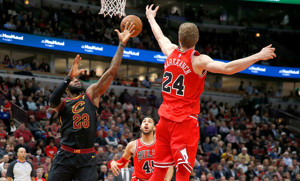 . Chicago Bulls\' Lauri Markkanen (24) bats away a pass intended for Cleveland Cavaliers\' LeBron James (23) during the first half of an NBA basketball game Monday, Dec. 4, 2017, in Chicago. (AP Photo/Charles Rex Arbogast)