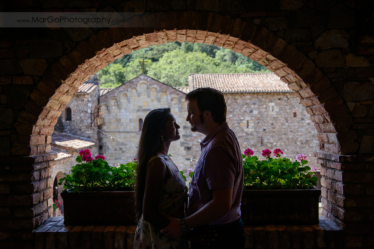 silhouette of man and woman looking at each other under brick arch during engagement session at Castello di Amorosa in Calistoga
