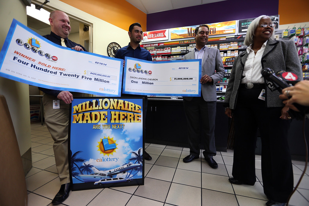 . California Lottery official John Reading; Parmeet Singh, the Dixon Landing Chevron gas station owner\'s son; his uncle Karam Singh, vice president of operations; and lottery official Mona Sanders, from left, pose with oversized checks in Milpitas, Calif., on Thursday, Feb. 20, 2014. The owners of the station received a $1 million bonus for having sold a winning Powerball lottery ticket worth $425 million. (Anda Chu/Bay Area News Group)