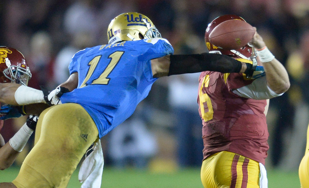. UCLA\'s Anthony Barr strips the ball from USC QB Cody Kessler in the 4th quarter. UCLA defeated USC 35 to 14 in a matchup of cross town rivals at the Los Angeles Memorial Coliseum in Los Angeles, CA.  photo by (John McCoy/Los Angeles Daily News)