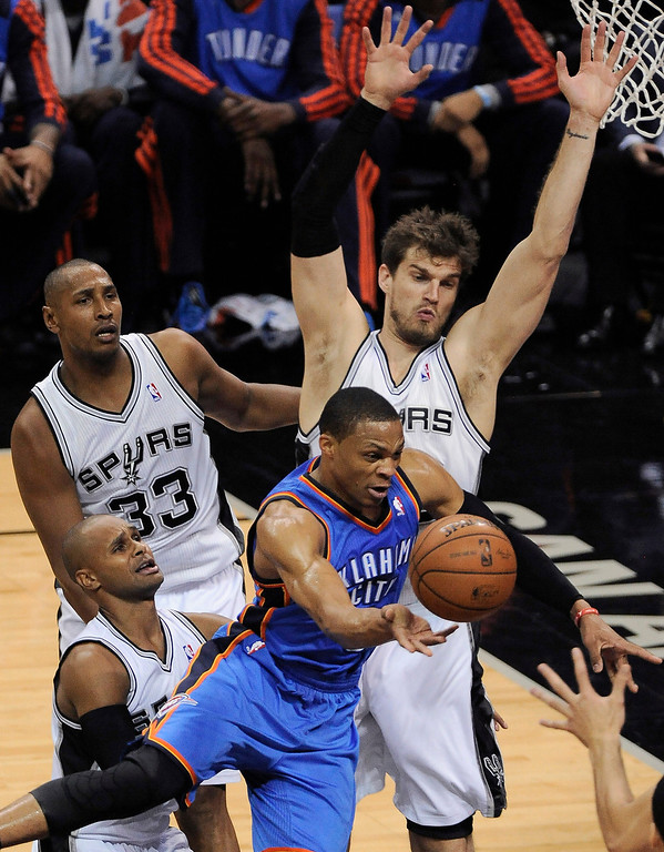 . Oklahoma City Thunder guard Russell Westbrook, front, passes the ball away as San Antonio Spurs\' Tiago Splitter, right rear, Boris Diaw (33) and Patty Mills defend during the first half of Game 5 of the NBA basketball playoff Western Conference finals, Thursday, May 29, 2014, in San Antonio. (AP Photo/Darren Abate)
