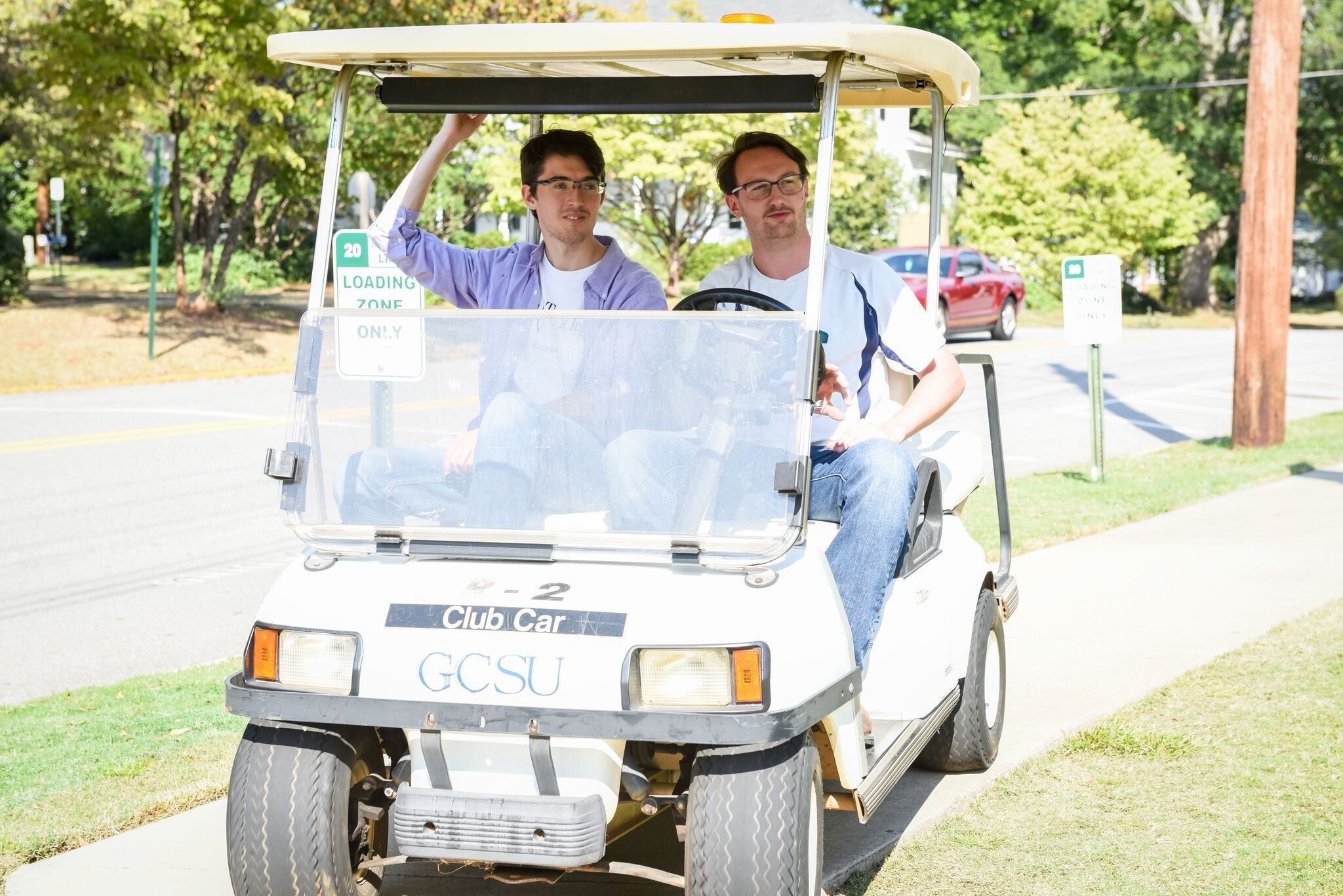 Alumni Dillon Vogt and Anderson Kendrick driving Georgia College's first solar-powered golf cart.
