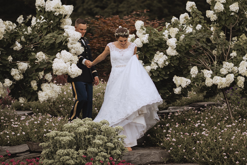 The bride leads the groom by the hand through the garden.