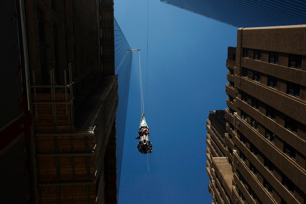 . A U.S. flag flies in the wind as the final piece of One World Trade Center\'s spire is lifted to the top of the building in New York, May 2, 2013. REUTERS/Lucas Jackson