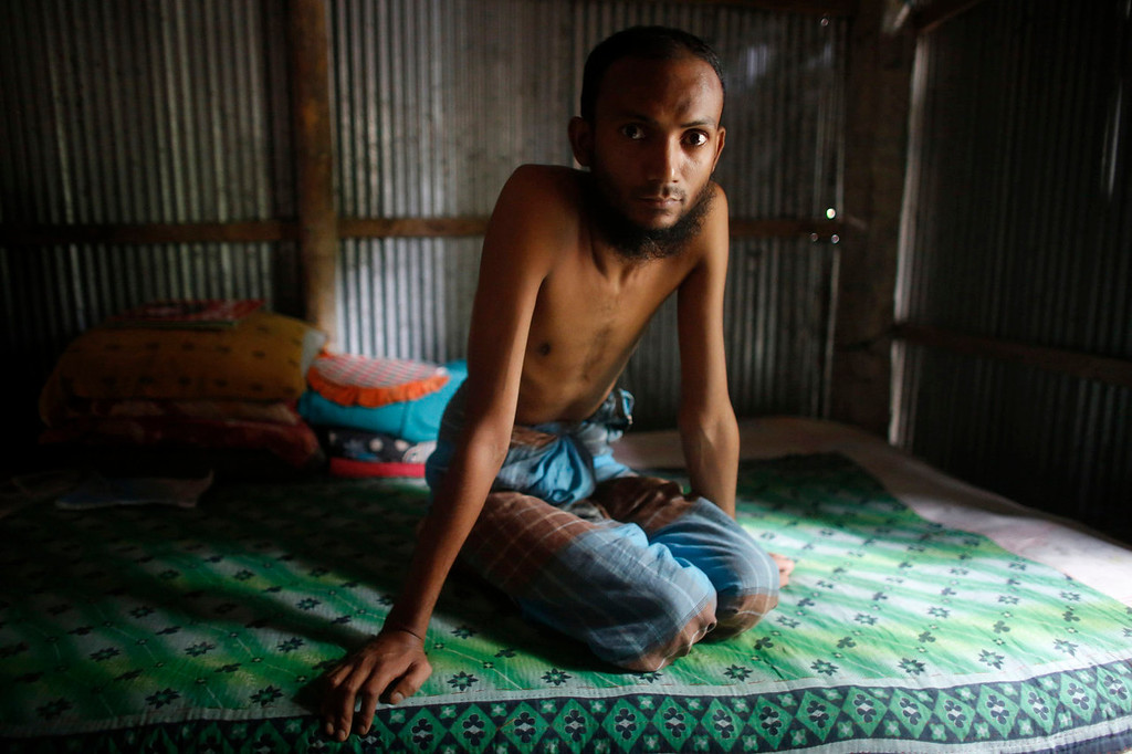 . Kamal Hossain, 28, sits on a bed as he describes the condition of his lungs inside his house at Burimari in Lalmonirhat district, Bangladesh July 9, 2013. Hossain says he suffers from silicosis, an incurable lung disease caused by the inhalation of silica dust as he used to work in a stone crushing factory for five years. The stone crushing industry in the Burimari land port area of Lalmonirhat, in the north of Bangladesh, produces lime powder for various industrial purposes. According to a report by the Bangladesh Institute of Labour Studies, those working in the industry run the risk of contracting silicosis. A researcher from the organization said that at least 18 workers in the Burimari area had died of complex silicosis over the last four years. International attention has been focused on workers\' safety in Bangladesh since the disaster at Rana Plaza, a garment factory complex which collapsed in April, killing 1,132 workers.  Picture taken July 9, 2013.  REUTERS/Andrew Biraj
