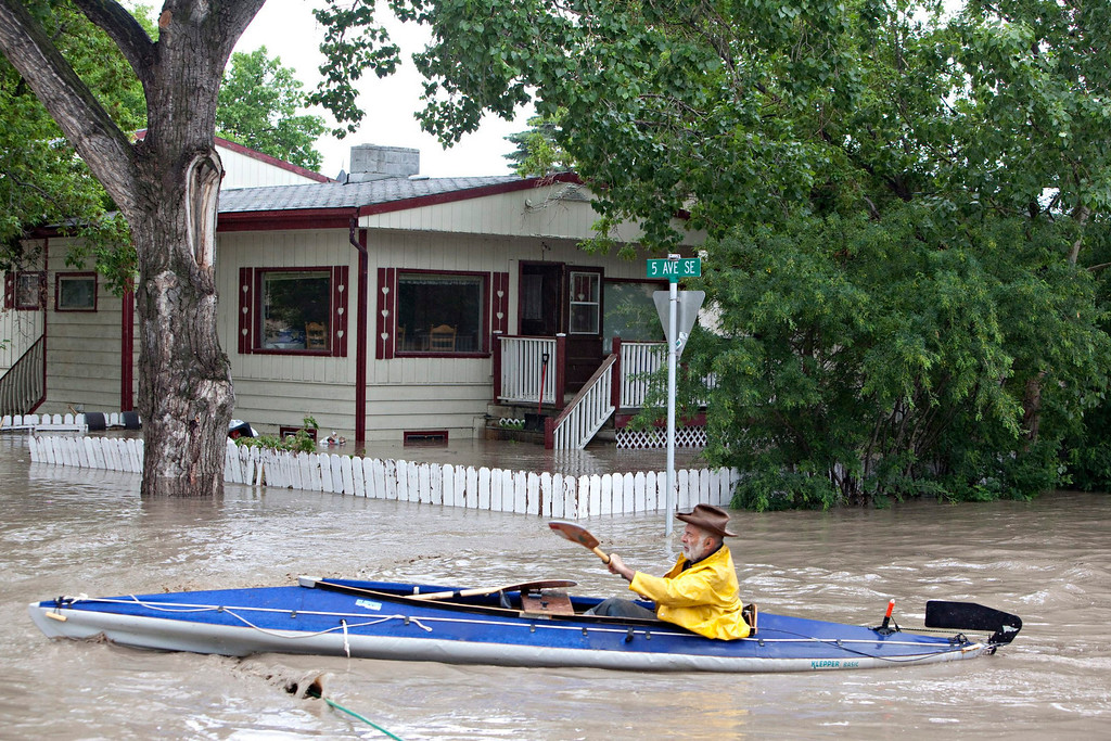 . A kayaker paddles down a flooded street in High River, Alberta on Thursday, June 20, 2013 after the Highwood River overflowed its banks. Calgary city officials say as many as 100,000 people could be forced from their homes due to heavy flooding in western Canada, while mudslides have forced the closure of the Trans-Canada Highway around the mountain resort towns of Banff and Canmore. (AP Photo/The Canadian Press, Jordan Verlage)