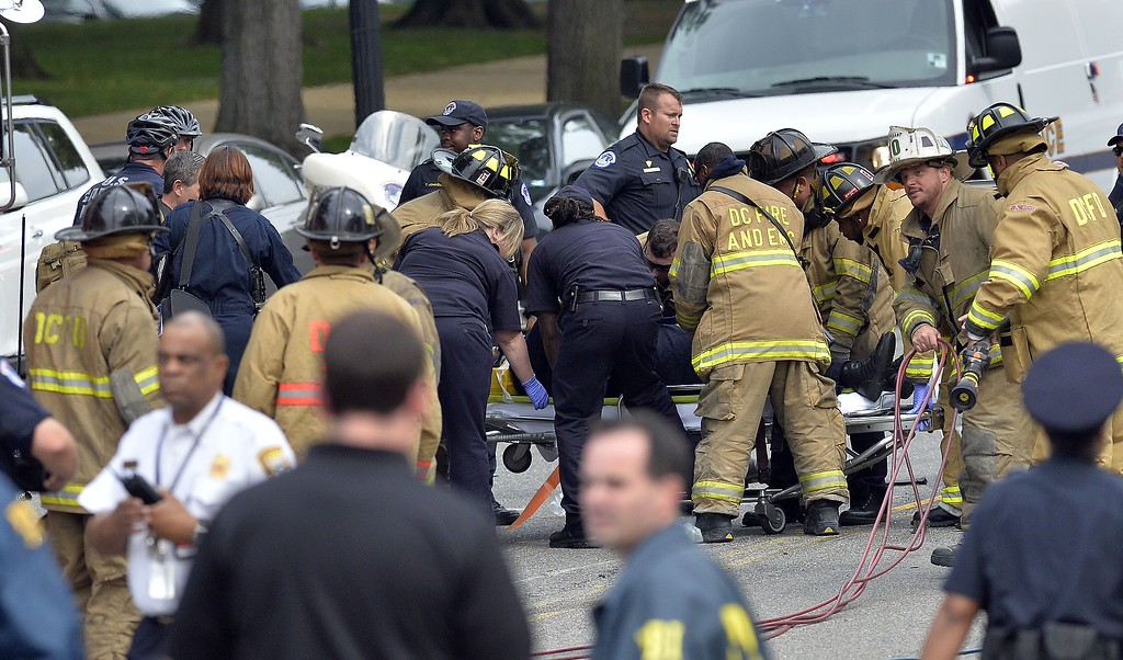 """. First responders put a police officer on the stretcher after pulling his out of a wrecked police car after shots fired were reported near 2nd Street NW and Constitution Avenue on Capitol Hill in Washington, DC, on October 3, 2013.  The US Capitol was placed on security lockdown Thursday after shots were fired outside the complex, senators said. \""""Shots fired outside the Capitol. We are in temporary lock down,\"""" Senator Claire McCaskill said on Twitter. Police were seen running within the Capitol building and outside as vehicles swarmed to the scene. AFP Photo/Jewel SAMAD/AFP/Getty Images"""