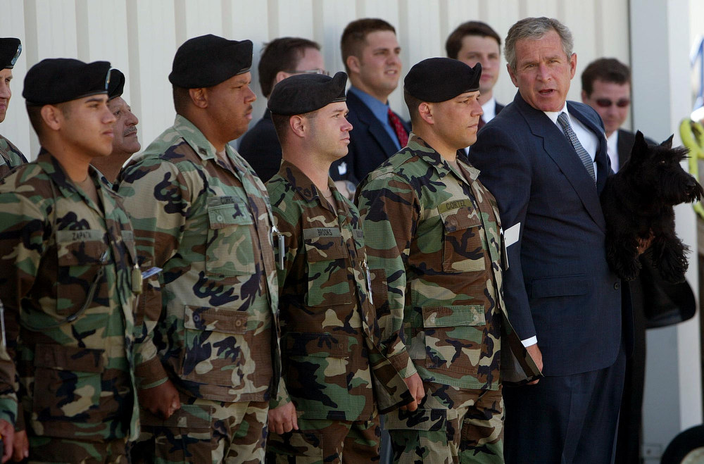 . President Bush, far right, holds his dog Barney as he poses for a photo with members of the 149th Infantry Military Police  unit from Ft. Hood, prior to his boarding Air Force One Monday April 21, 2003 in Waco, Texas. The president is returning to Washington after spending the Easter weekend with his family at his ranch at nearby Crawford. (AP Photo/Pablo Martinez Monsivais)