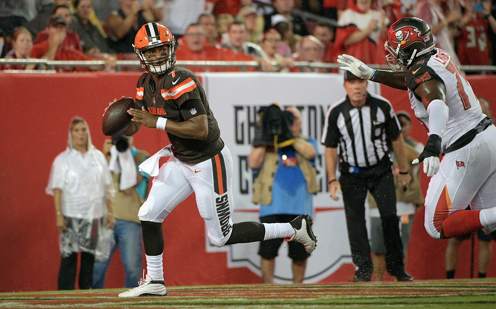 . Cleveland Browns quarterback DeShone Kizer (7) eludes Tampa Bay Buccaneers defensive end DaVonte Lambert (75) during the second quarter of an NFL preseason football game Saturday, Aug. 26, 2017, in Tampa, Fla. (AP Photo/Phelan Ebenhack)
