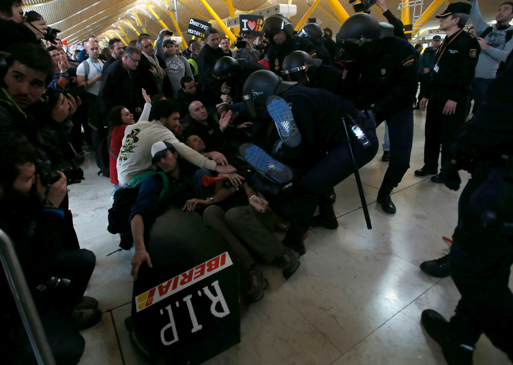 . Iberia workers clash with Spanish riot police officers at Terminal 4 of Madrid\'s Barajas airport February 18, 2013. Workers at loss-making Spanish flag carrier Iberia began a five-day strike at midnight on Monday, grounding over 1,000 flights and costing the airline and struggling national economy millions of euros. REUTERS/Sergio Perez