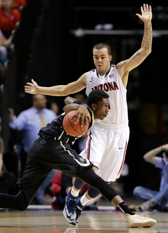 . Colorado\'s John Hopkins drives against Arizona\'s Gabe York during the first half of an NCAA college basketball game in the semifinals of the Pac-12 Conference on Friday, March 14, 2014, in Las Vegas. (AP Photo/Julie Jacobson)