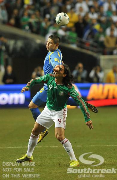 Mexico's Forward Aldo De Nigris (#9) gets an arm to the face in Soccer action between Bosnia-Herzegovina and Mexico.  Mexico defeated Bosnia-Herzegovina 2-0 in the game at the Georgia Dome in Atlanta, GA.