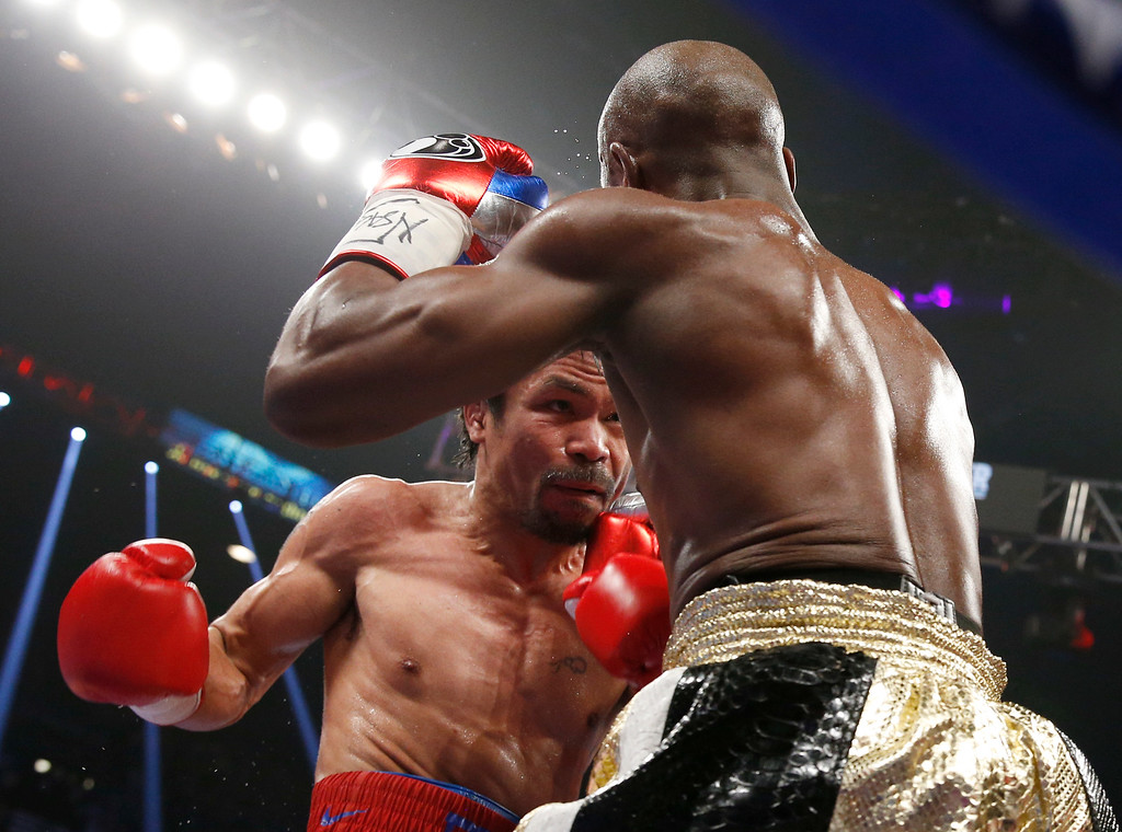 . Manny Pacquiao, left, from the Philippines, trades blows with Floyd Mayweather Jr., during their welterweight title fight on Saturday, May 2, 2015 in Las Vegas. (AP Photo/John Locher)