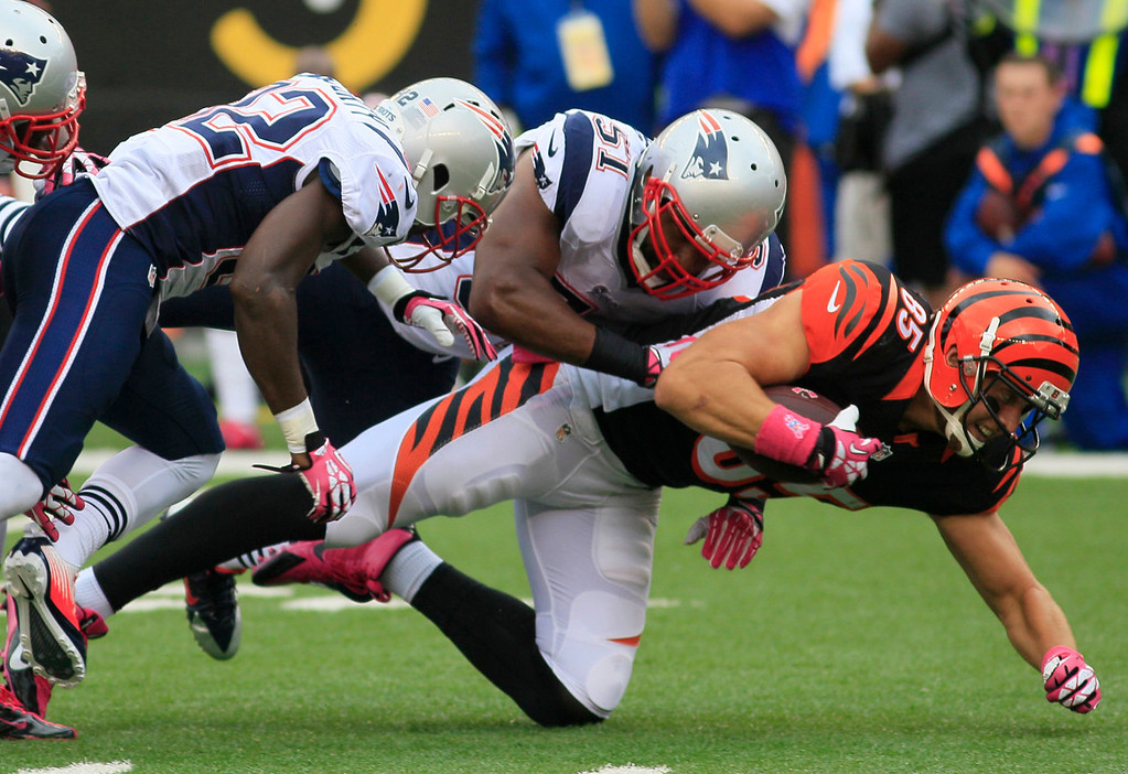 . Cincinnati Bengals tight end Tyler Eifert (85) is tackled by New England Patriots outside linebacker Jerod Mayo (51) and free safety Devin McCourty (32) after a short gain in the first half of an NFL football game, Sunday, Oct. 6, 2013, in Cincinnati. (AP Photo/Tom Uhlman)